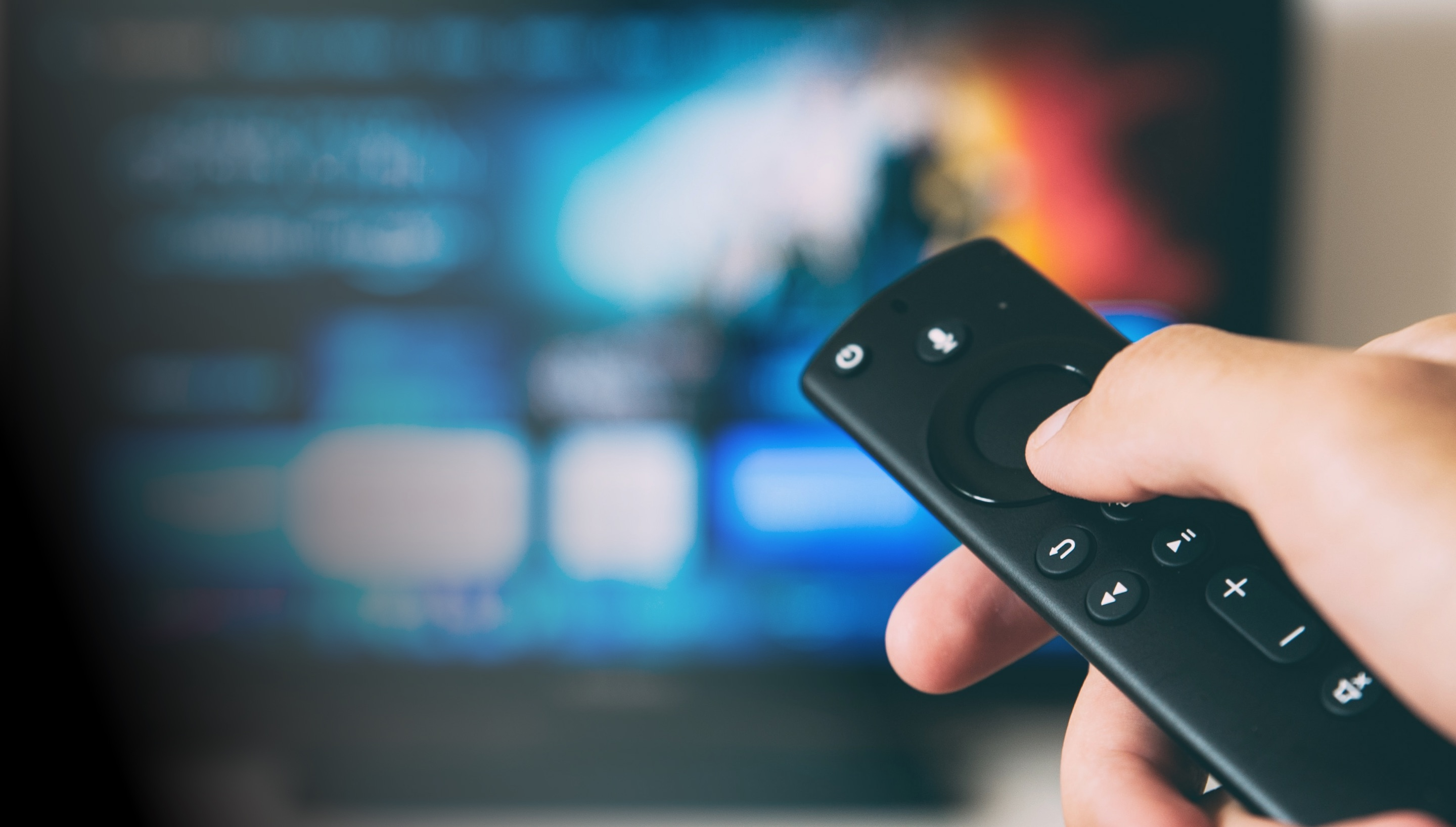 A person selecting streaming with a remote directed toward a television