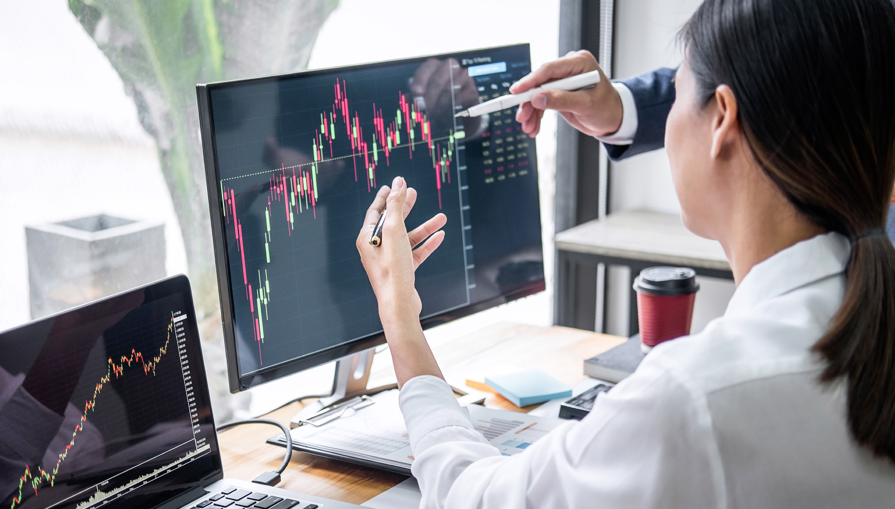 Woman working on a computer that has a stock trading chart